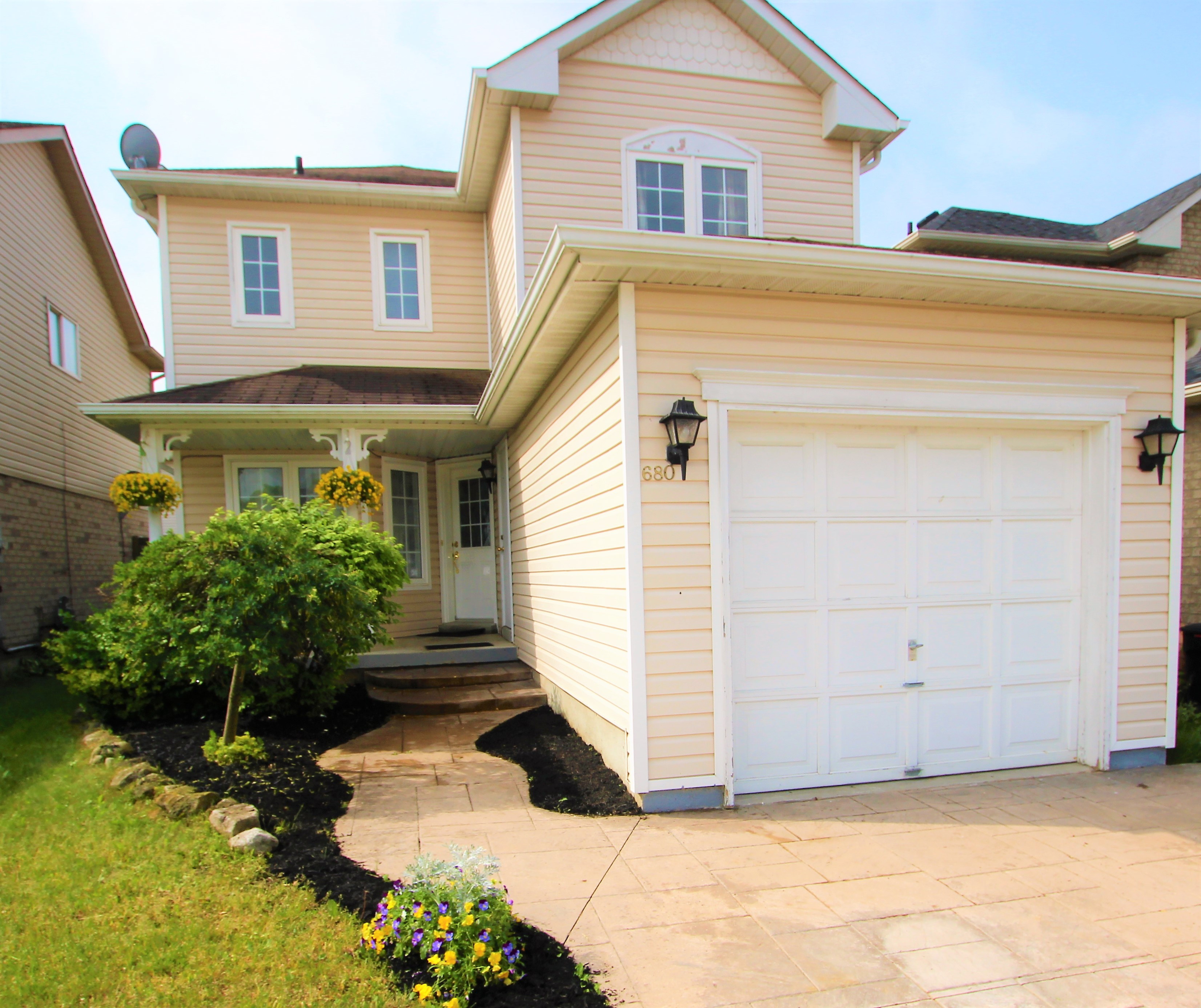 Front view of the house showing the parking gate and main door at 680 Langlaw Drive