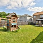 Image of the spacious back yard with s wooden playhouse and a covered picnic table at 6 Warner Lane